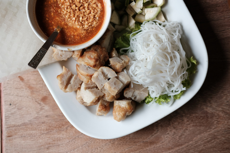 minced pork sausage, fermented rice noodle & vegetable served with chili sauce. vietnamese summer roll food called Nem Nuong Xa