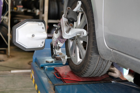 car tyre clamped with  aligner reflector adjustment tool for wheel alignment check in auto garage repair service