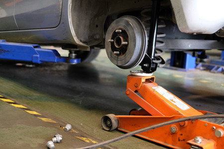 car lift up for shock absorber & spring replacement in auto service repair garage 스톡 콘텐츠