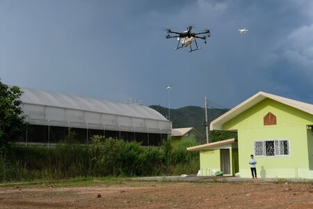Chiang Mai, Thailand - September 7, 2018: man flying agriculture drone for spraying liquid fertilizer on farm land in Maejo university. Redakční