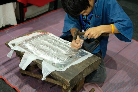 Chiang Mai, Thailand - September 9, 2018: Silversmith craftsman carving pattern on silver plate, metal engraving at unseen lanna expo at Chiang Mai International Exhibition and Convention Centre in Chiang Mai, Thailand on September 9, 2018.