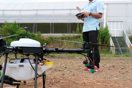 Chiang Mai, Thailand - September 7, 2018: man controlling agriculture drone for spraying liquid fertilizer on farm land in Maejo university.