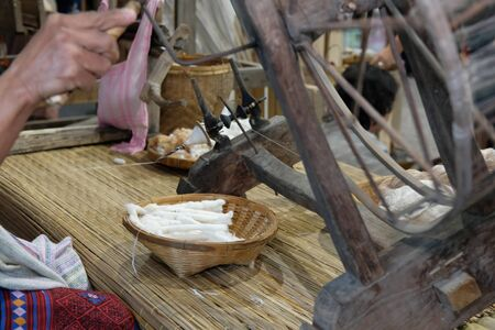 Chiang Mai, Thailand - September 9, 2018: woman spinning cotton into thread with traditional wheel at unseen lanna expo at Chiang Mai International Exhibition and Convention Centre in Chiang Mai, Thailand on September 9, 2018.