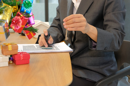 real estate agent with house key using stamper for stamping approved on mortgage loan contract agreement document during christmas