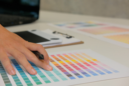 graphic interior designer choosing color from swatch sample catalogue palette guide at workplace. artist design & idea for creativity project.