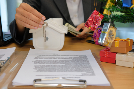 real estate agent with house model banknote & key. buying selling renting real estate property