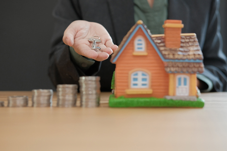 agent with coins stack house model and key. saving money for buying real estate property 版權商用圖片