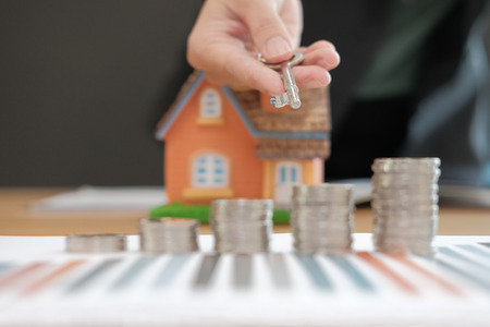 Agent with coins stack house model and key. saving money for buying real estate property