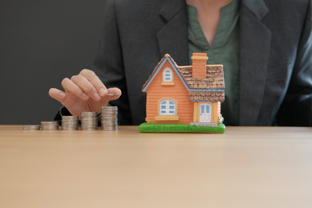hand putting coins on stack with house model. saving money for buying house property. real estate investment Stock Photo