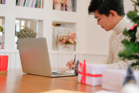 man wearing cream sweater writing christmas letter greeting card holiday wishes with xmas decoration.
