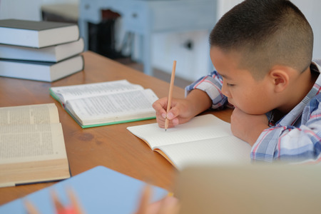 young little asian kid boy schoolboy writing drawing on notebook. child children doing homework. childhood education