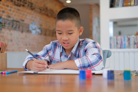 little asian kid boy child schoolboy drawing picture. children leisure activity at home Stock fotó