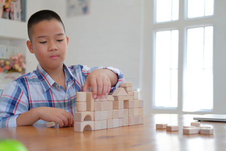 young little asian kid boy child children schoolboy playing wood block toy. learning education concept