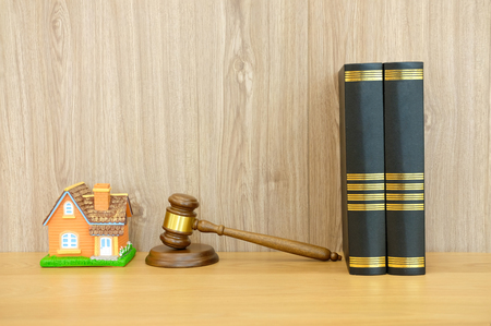 judge gavel law book & home house model on wooden desk. real estate dispute & property auction concept