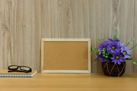 cork board notebook glasses artificial flower on wooden table at office workplace