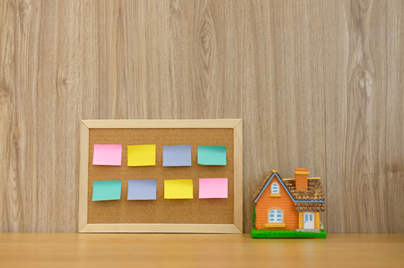sticky notes paper reminder on cork board & house model on wooden desk. real estate investment. property buying mortgage loan