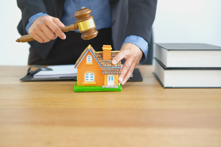 lawyer with judge gavel knocking house model at courtroom. real estate dispute & property auction concept