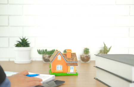 real estate agent realtor organizing plan with house model on desk. buying selling & renting property