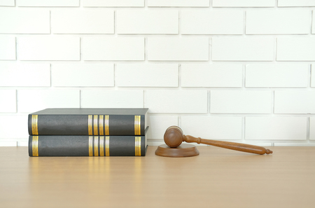 legal law book & judge gavel near white brick wall. lawyer attorney justice workplace.