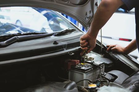 mechanic opening closing checking car battery in automobile repair service garage