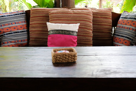 pink pillow on wooden settee bench on terrace patio near garden