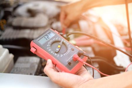 Mecánico de automóviles comprobar el voltaje de la batería del coche mediante un voltímetro multímetro en la estación de servicio de reparación
