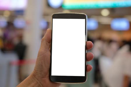 mano che tiene lo smartphone mobile al terminal dell'aeroporto