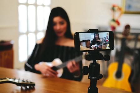blogger live broadcasting music instrument tutorial on social media. vlogger recording online vlog video. influencer marketing Reklamní fotografie