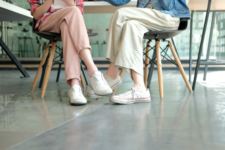 girl teenager friends legs wearing white sneakers sitting talking together. friendship leisure lifestyle