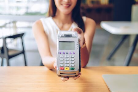woman with credit card swiping machine. shopping lifestyle and payment with nfc technology Banco de Imagens