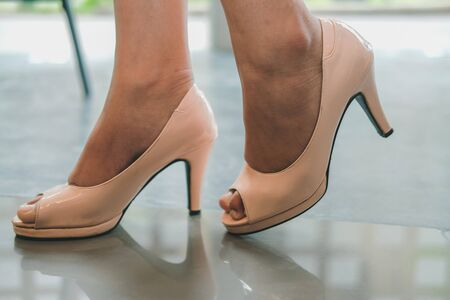 vrouwelijke vrouwenbenen die roze schoenen met hoge hakken dragen