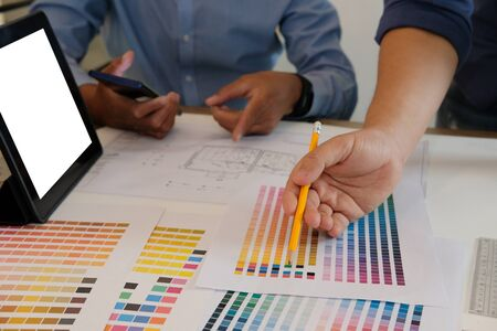 architect interior designer working with architectural drawing of house & color swatch catalog