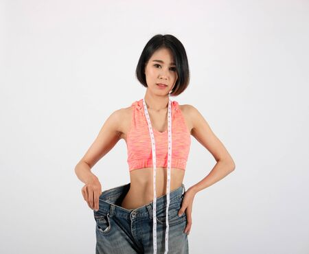 sporty fitness woman in loose jeans after losing weight on white background. healthy sport lifestyle