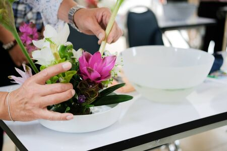 florist arranging flower bouquet in vase. people in floristry class course workshop