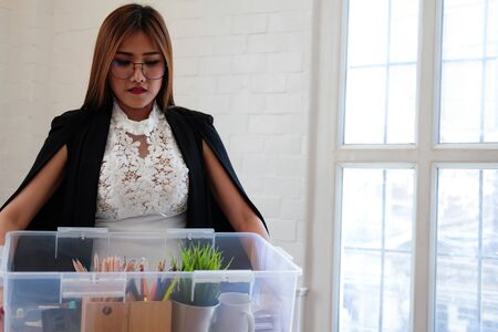frustrated woman holding box containing personal belongings after being fired and layoff by employer. resignation concept