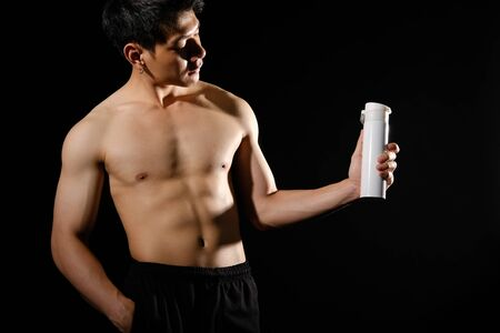 portrait of athletic muscular bodybuilder man with torso six pack abs holding protein drink. fitness workout concept