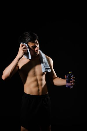 portrait of athletic muscular bodybuilder man with torso six pack abs holding water bottle. fitness workout concept