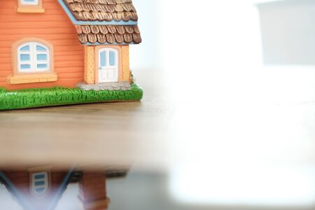 house home model on wooden desk. realtor real estate agent workplace. buying selling renting property