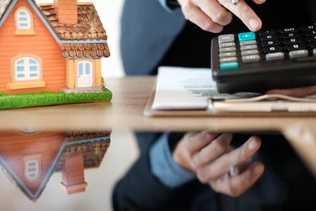 businessman calculating budget with calculator. saving money for buying home house property. real estate investment