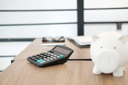 calculator piggy bank on office desk. accounting saving for business finance