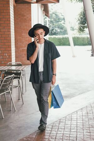man holding paper shopping bags & talking on mobile smart phone. consumerism lifestyle 写真素材