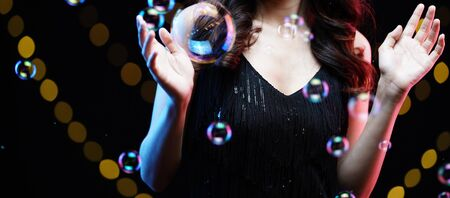 woman in black evening dress with bubble & yellow bokeh