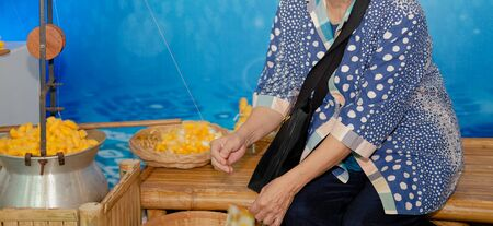 old woman & yellow silkworm cocoon shell for making thread producing Thai silk fabric textile