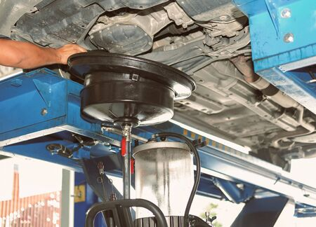 vehicle lift up by hydraulic for motor oil change and transmission inspection. changing engine oil in automobile repair service. maintenance and checkup in car workshop.