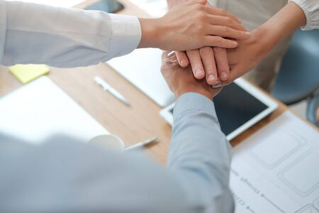 businessman businesswoman joining united hand, business team touching hands together after complete a deal in meeting. unity teamwork partnership corporate concept.