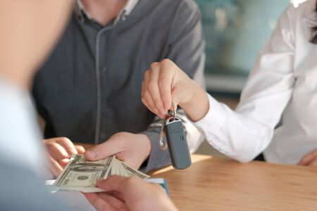 client pay for new car. salesman dealer giving key to owner. car sale & dealership in auto business