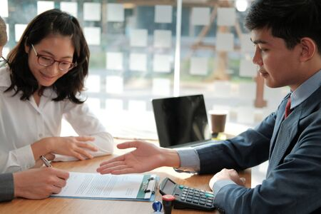 couple buying renting house car signing mortgage insurance purchase order contract with realtor real estate agent. architect designer closing dealing with customer Stock Photo