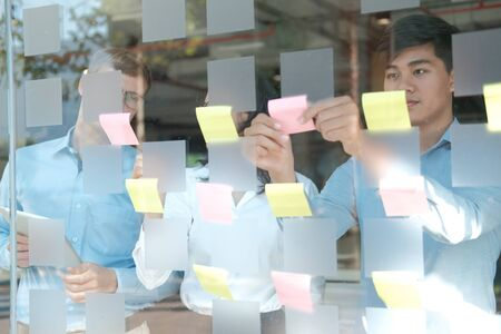 business people working planning discussing idea with sticky reminder note on glass wall at workplace