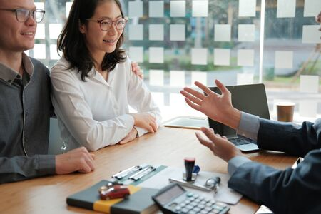 couple consulting lawyer about buying renting house car. insurance broker financial advisor giving legal advice to customer.realtor selling real estate property to client Stock Photo
