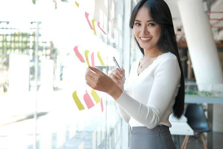 businesswoman woman thinking planning with adhesive notes on glass wall at workplace. Sticky note paper reminder schedule for creative idea & business brainstorming